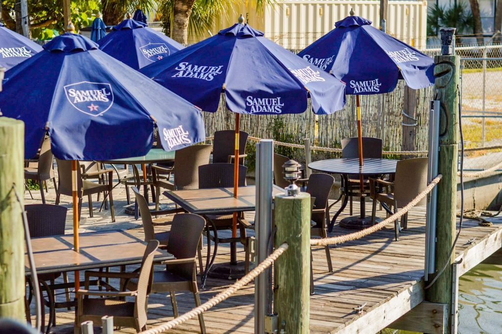 tables with blue umbrellas on a dock