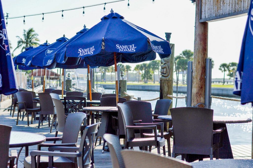 tables with blue Samuel Adams umbrellas overlooking a canal
