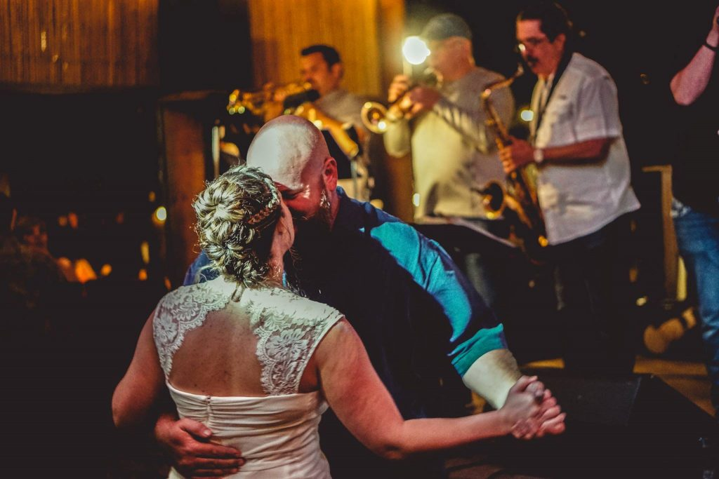 bride and groom dancing with band in background