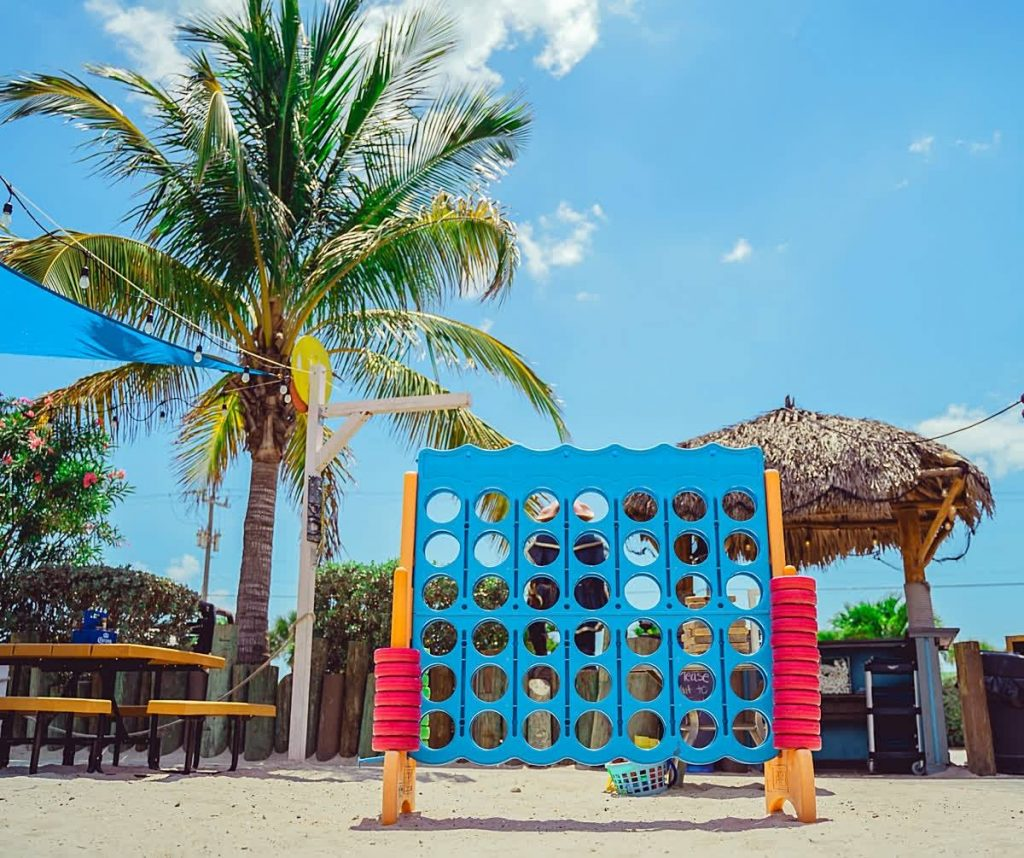 jumbo connect four game on beach with palm tree
