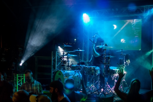 Musician singing and playing drums in moody blue lights