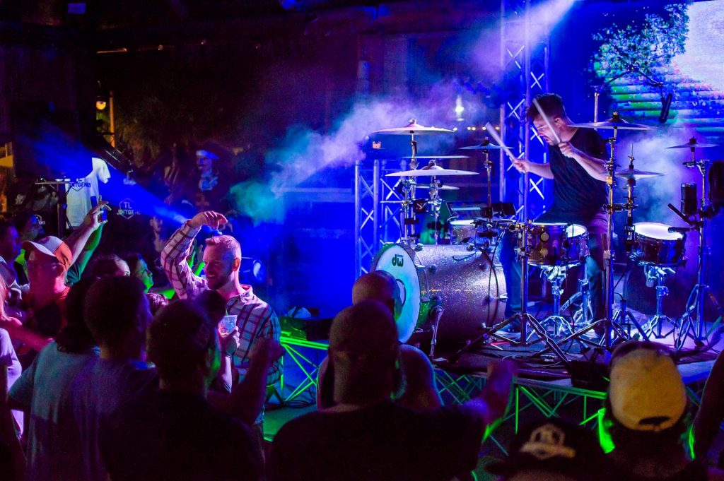 Musician singing and playing drums in moody blue and purple lights