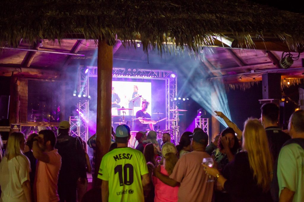 crowd at a concert under a tiki roof