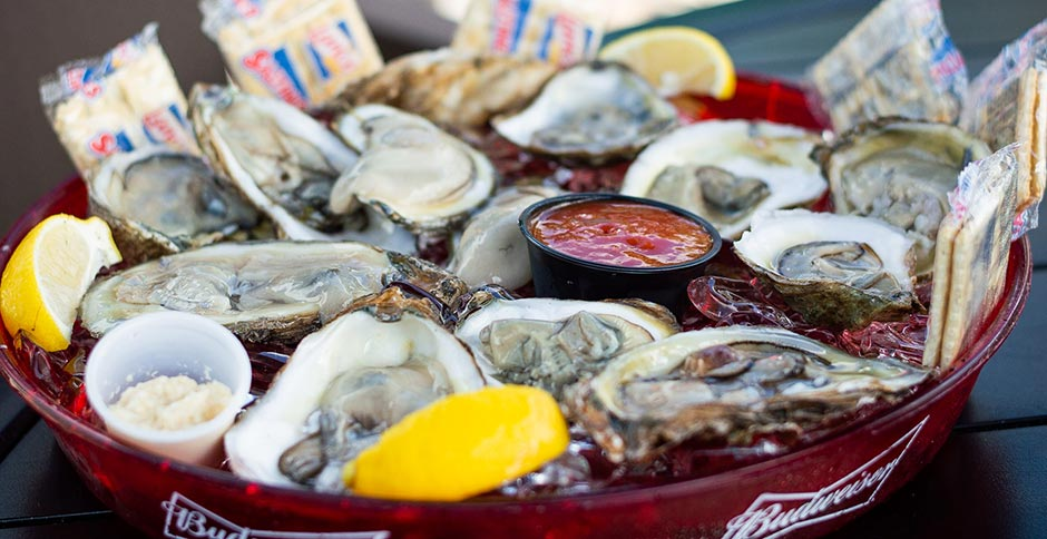 oysters on the half shell with lemon, crackers and dipping sauce