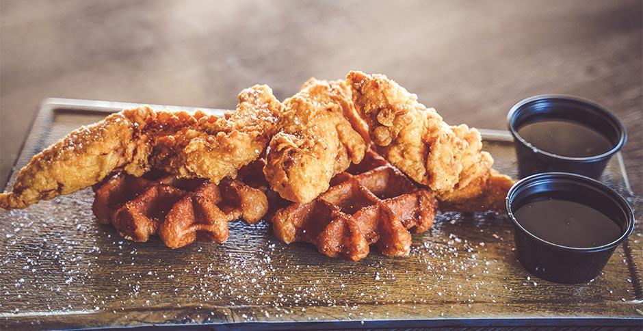 two waffles topped with fried chicken and served with dipping sauces